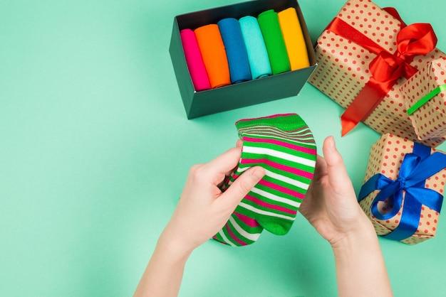 여자 손에 선물로 면 양말의 다채로운 컬렉션입니다. 선물.