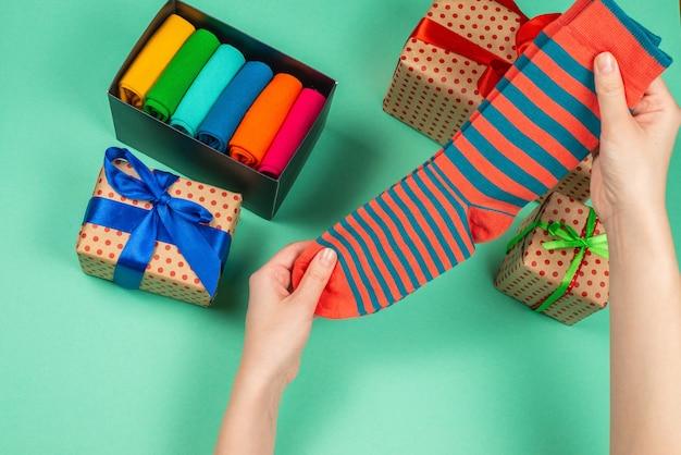 女性の手への贈り物としての綿の靴下のカラフルなコレクション。贈り物。