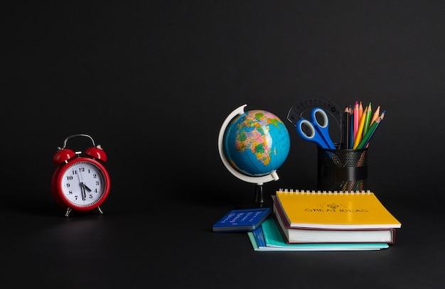 Красочная коллекция школьных принадлежностей на черном фоне. обратно в школу. отличные идеи