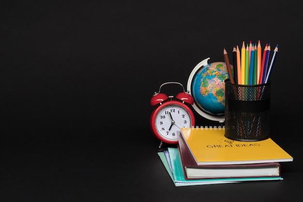 검은 배경에 설정된 학용품의 다채로운 컬렉션입니다. 학교로 돌아가다. 훌륭한 아이디어