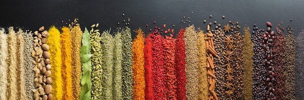 Colorful collection spices and herbs on background black table.