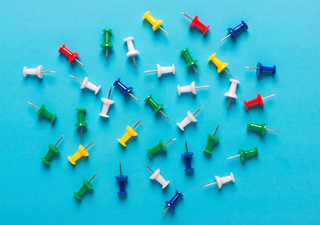 Colorful collection of a thumbtack on blue