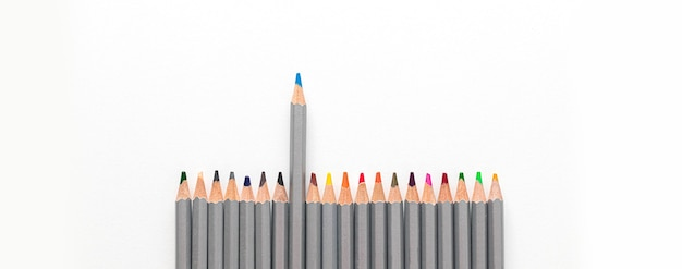 Colorful colored pencil and white paper on white table background