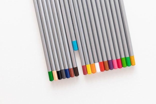 Colorful colored pencil and white paper on a white table background