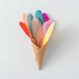 羽とアイスクリームコーンで作られたカラフルな構成。ミニマル自由奔放に生きるスタイルの色の概念。平置きの夏の食べ物の背景。