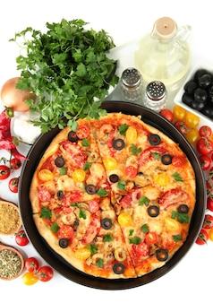 白い背景のクローズアップでおいしいピザ、野菜、スパイスのカラフルな構成