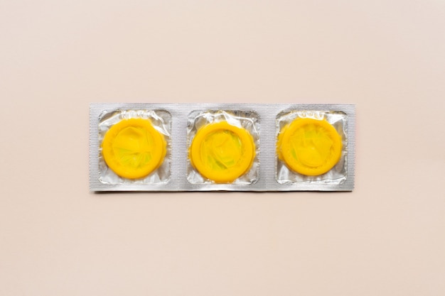 베이지 색 표면에 노란색 콘돔으로 다채로운 구성. 안전한 성관계 및 피임 개념