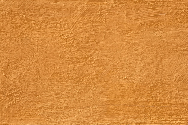 カラフルなコンクリートの壁、小さなテクスチャの詳細とセメントの背景ペイントの明るく暖かい黄色のビンテージスタイル。古いテクスチャ表面