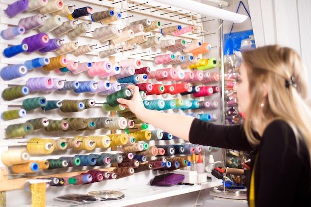 Красочные конусы и катушки ниток в ателье. пошив, швейная промышленность, концепция дизайнерской мастерской.