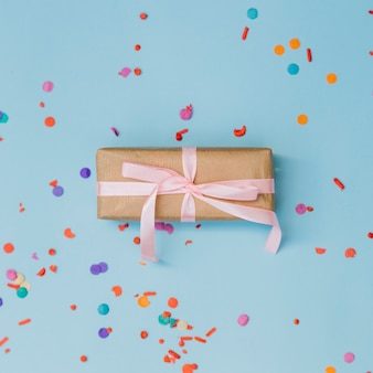 Colorful confetti around the wrapped gift box tied with pink ribbon