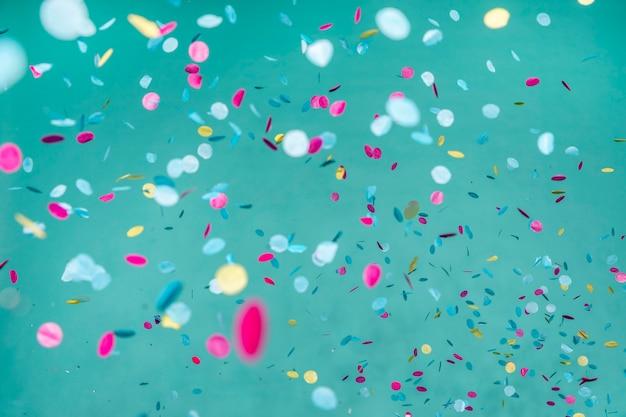 파란 벽에 화려한 색종이 배열