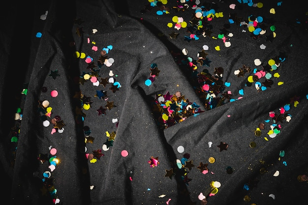 Colorful confetti on dark crumpled cloth