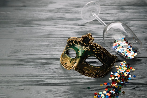 Colorful confetti fallen from wine glass with carnival mask on wooden textured background