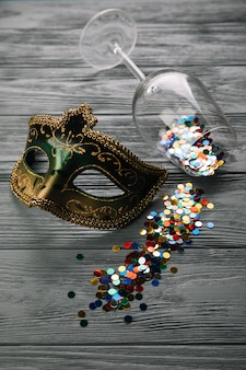 Colorful confetti fallen from wine glass with masquerade carnival feather mask on wooden table