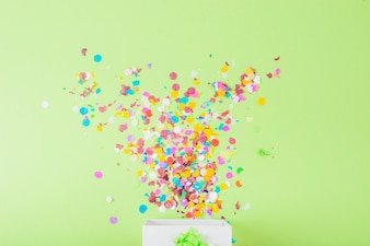 Colorful confetti falling in the white box over the green backdrop