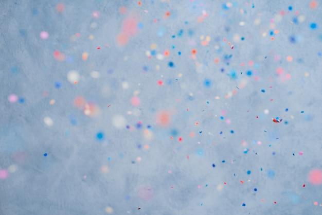 파란색 배경에 떨어지는 화려한 색종이