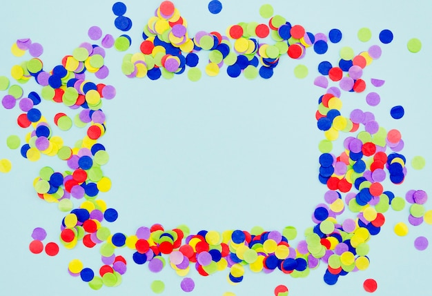 Colorful confetti frame on blue background