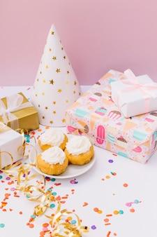 カラフルな紙吹雪。ギフト用の箱。パーティーハットと白いテーブルの上のおいしいカップケーキ