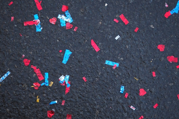 Colorful confetti lie on the cold dark asphalt after the holidays