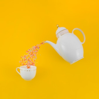Colorful confetti pouring from white tea pot in the ceramic cup against yellow background