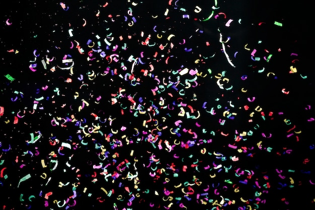 Colorful confetti space. red, blue, green, yellow on black. carnival decoration