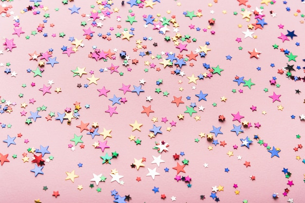 Colorful confetti stars on pink background