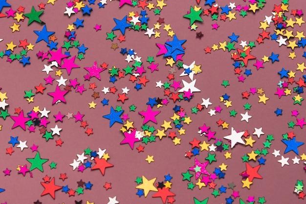 Colorful confetti stars on purple background