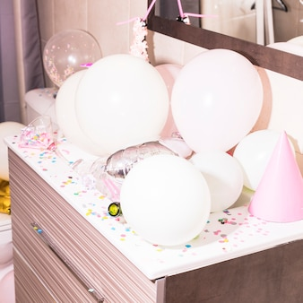 Colorful confetti and white balloons on wooden desk