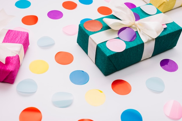 Colorful confetti on wrapped gift box with ribbon against white background