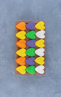 Colorful cookies on the board , on the marble background.
