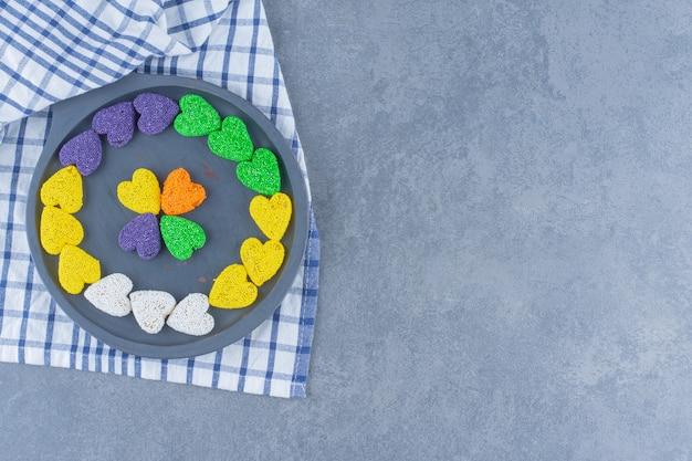 Разноцветное печенье на доске на полотенце, на мраморной поверхности
