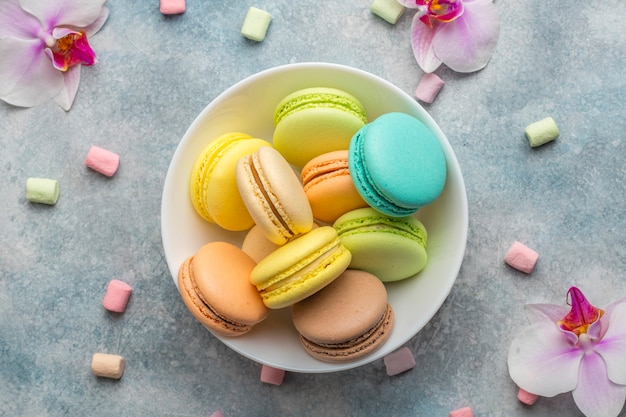 Colorful cookies macarons on the plate and airy marshmallows