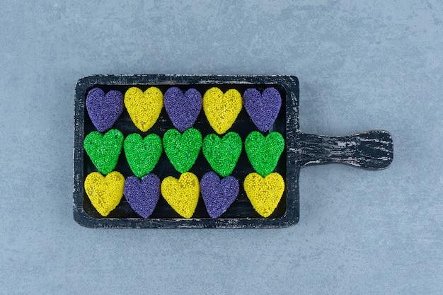 Разноцветное печенье на доске, на мраморном столе.