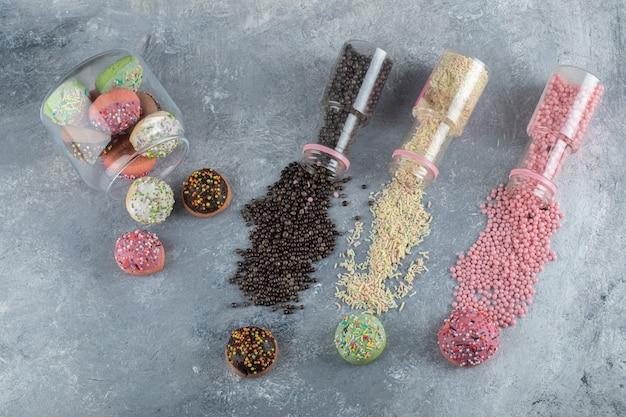 Biscotti colorati con caramelle in barattolo di vetro con mazzetto di granelli.