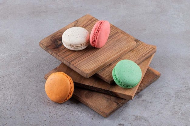 Colorful cookies on wooden board stack over grey background.