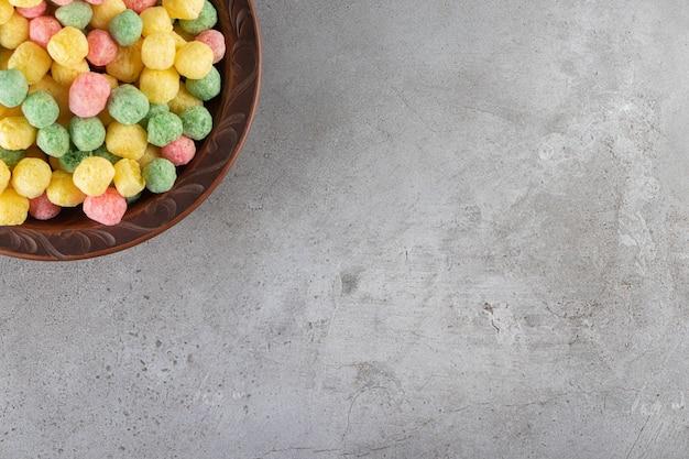 大理石のテーブルの上に、ボウルにカラフルなコーンボール。