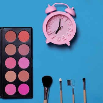Colorful cosmetics brushes, eyeshadows, blush, alarm clock on a blue background. makeup set. flat lay, copy space, background for design. time for makeup
