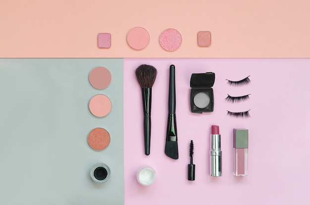Colorful cosmetics lying on pastels surface. flatlay