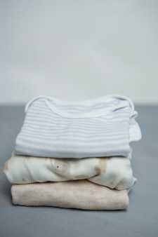 Colorful cotton folded clothes stack on white table empty space background,baby laundry.