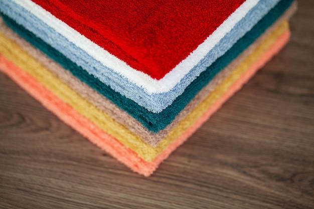 木製のテーブルのバスルームにカラフルな綿のタオル