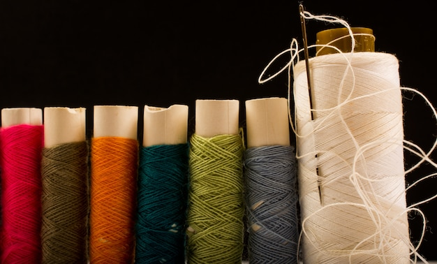 Colorful cotton yarns on rolls for sewing. thread spools used in fabric and textile industry