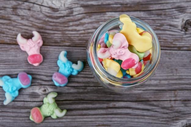 ガラスの瓶から散らばったカラフルな牛グミキャンディー