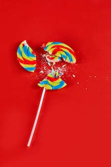 Colorful cracked lollipop on red surface.