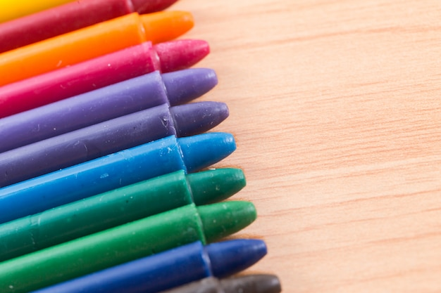 Colorful crayon colors on wood background
