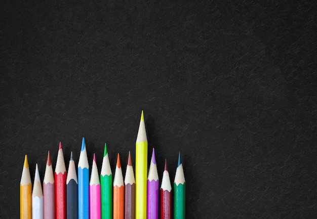Colorful crayon pencils on black canvas with copy space.