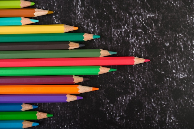 Colorful crayon pencils with triangle shape on white surface with copy space. top view