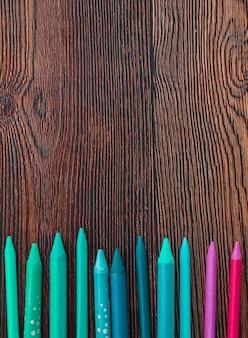 나무 배경의 하단에 배열하는 다채로운 크레용