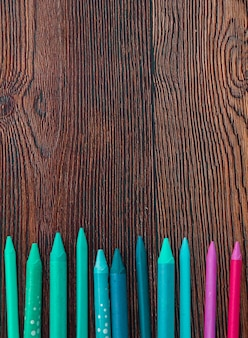 Colorful crayons arranged at the bottom of wooden background