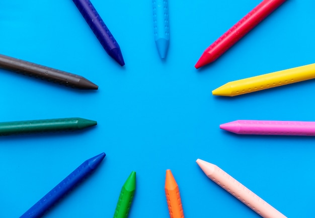Colorful crayons forming a circle top view on a cyan background