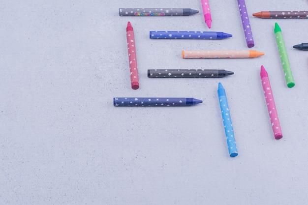 Цветные мелки или карандаши на сером.